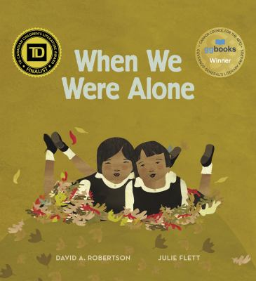 The cover of the book When We Were Alone by David A. Robertson featurses two Native American children wearing residential school uniforms lying in a pile of fall leaves.